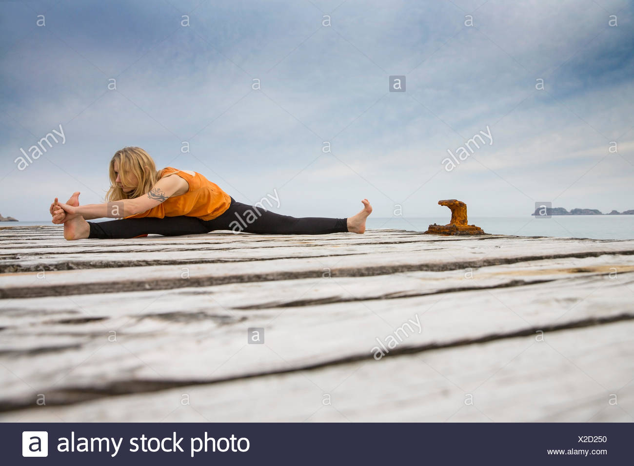 Mid adult woman practicing yoga on wooden sea pier - Stock Image