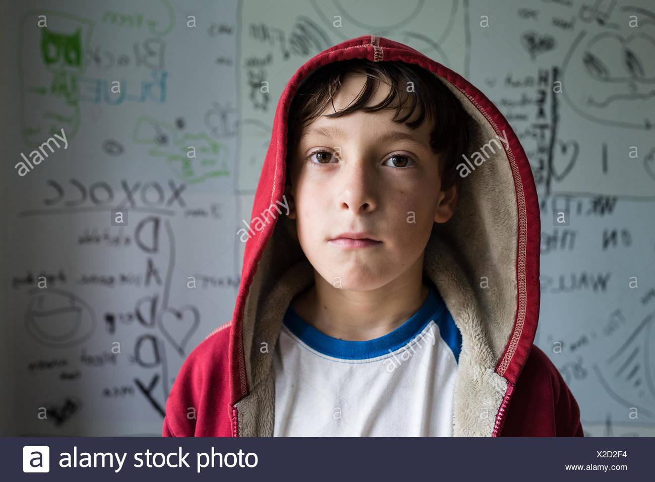 Portrait of boy wearing a red hooded sweatshirt. - Stock Image