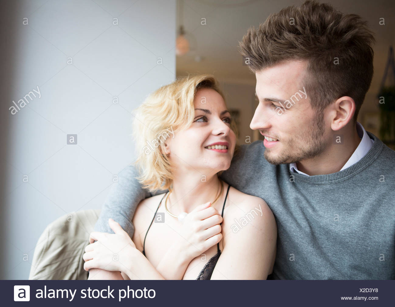 Happy young couple looking at each other in cafe - Stock Image