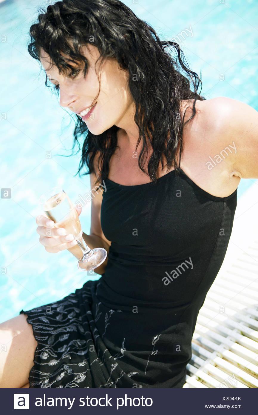 Frau Schwarzhaarig Pool Beckenrand Sitzen Jung Kleid Sommerkleid Barfuss Entspannt Gluecklich Trinken Sekt Champagner Glas Freud - Stock Image