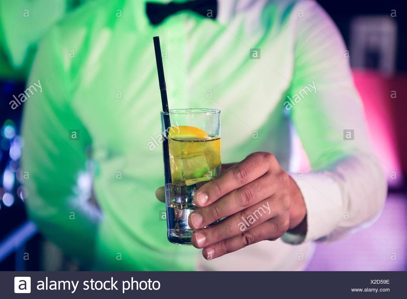 Bartender serving glass of gin - Stock Image