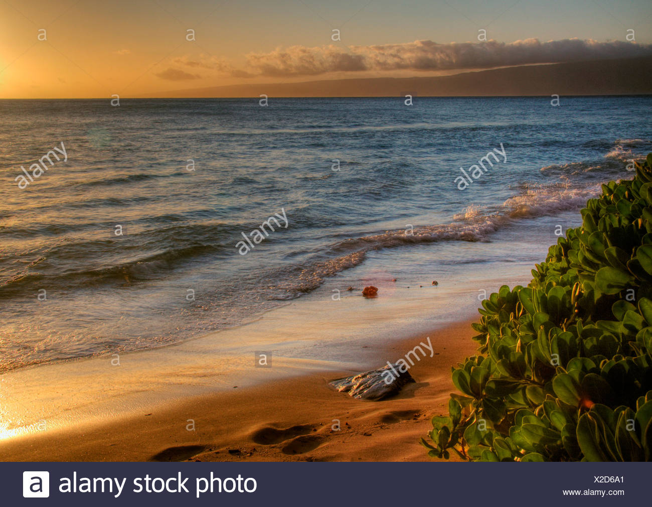 Sunsets warm glow on golden sand beach, West Maui, Hawaii. Island of Lanai in the distance - Stock Image