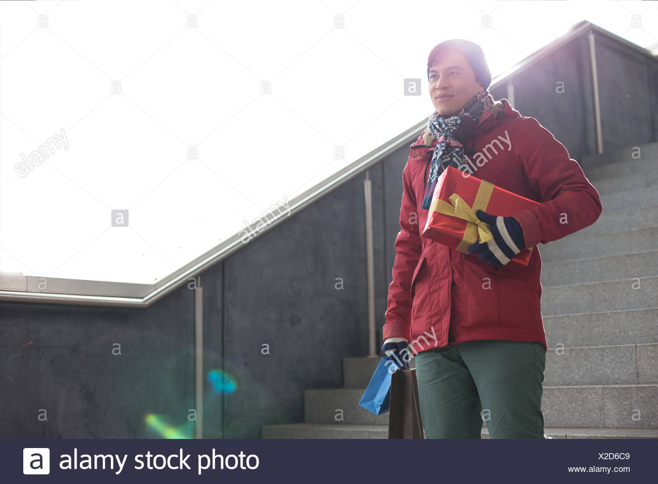 Smiling man holding gifts while moving down steps Stock Photo