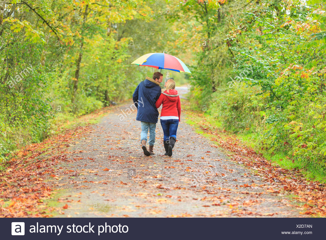 Young couple strolling along country lane with colorful umbrella - Stock Image
