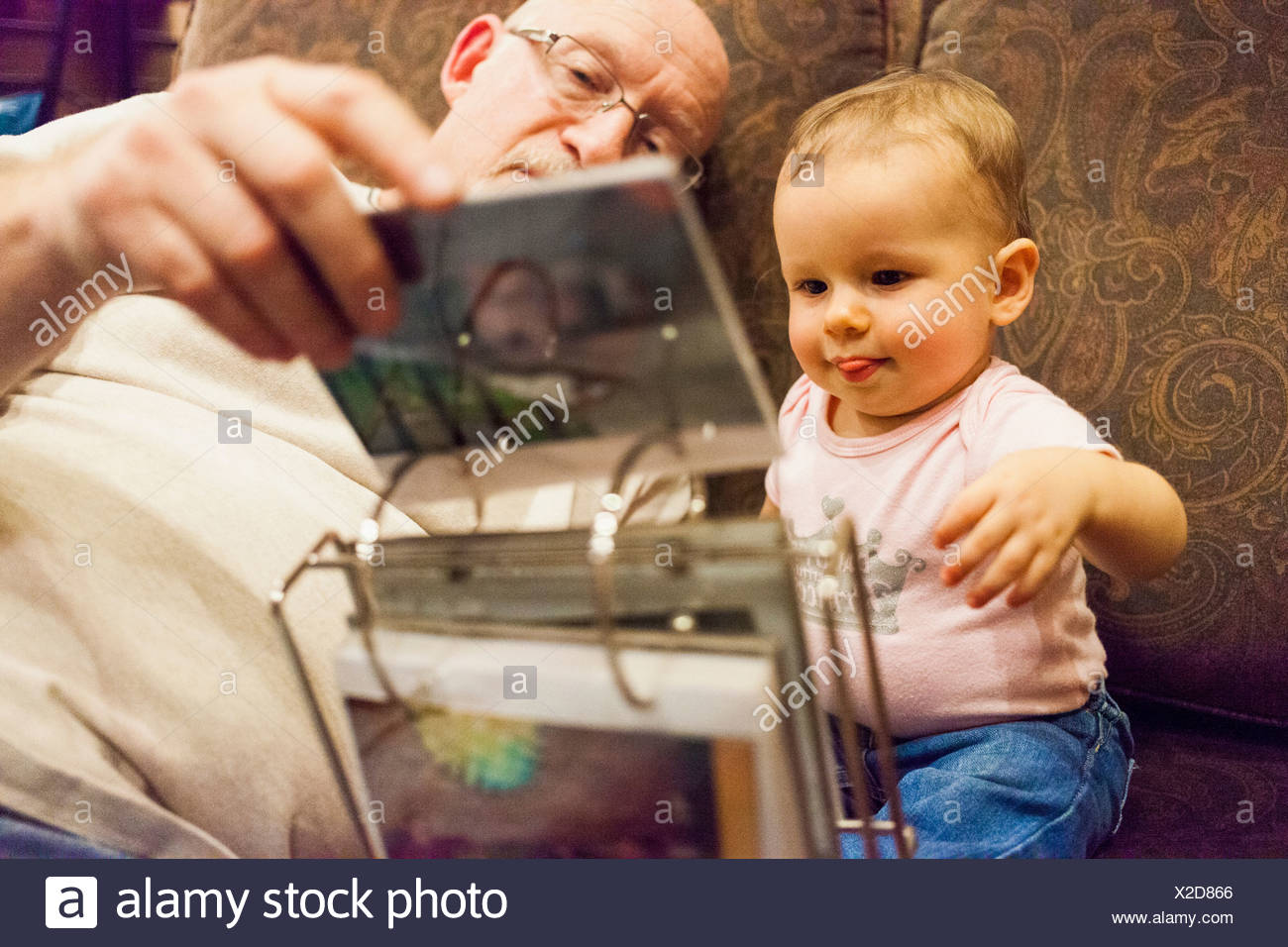 Grandfather and granddaughter looking at photo album - Stock Image