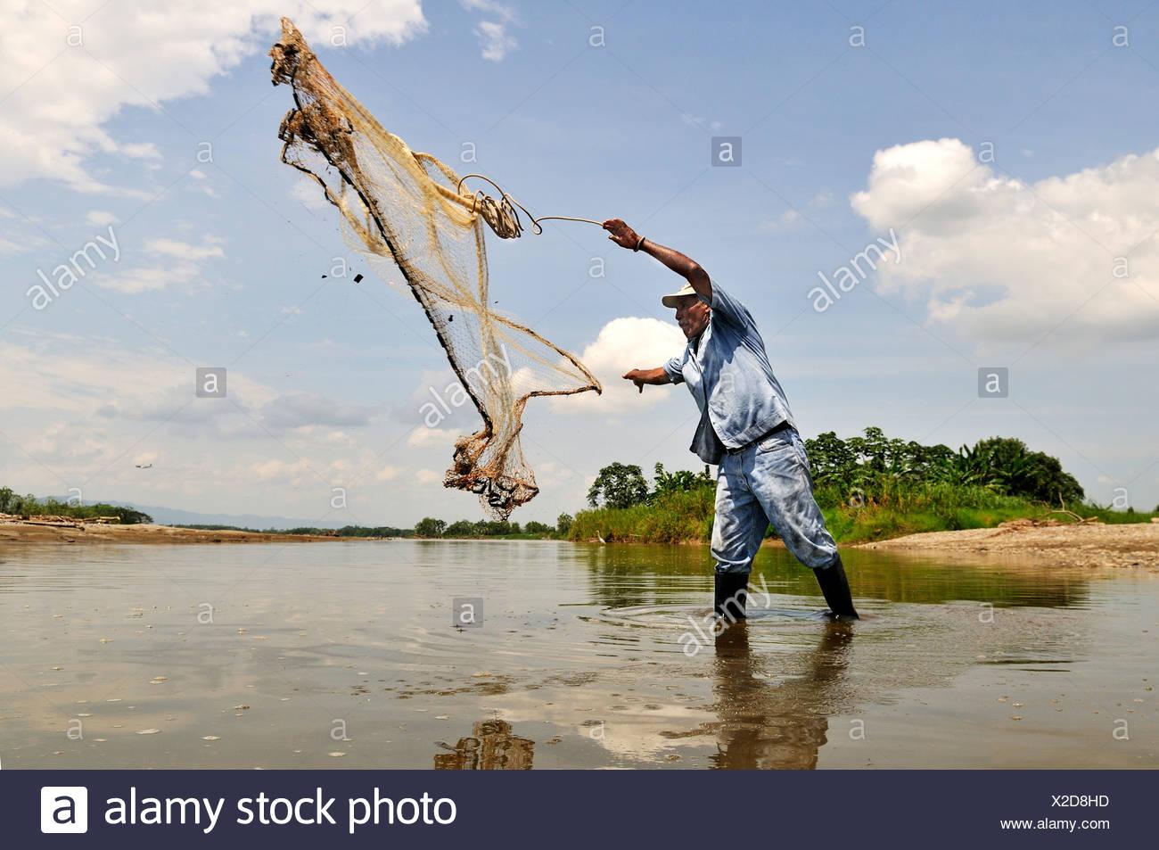 Fisherman tossing a net into the Rio Magdalena River, La Dorada, Caldas, Colombia, South America - Stock Image