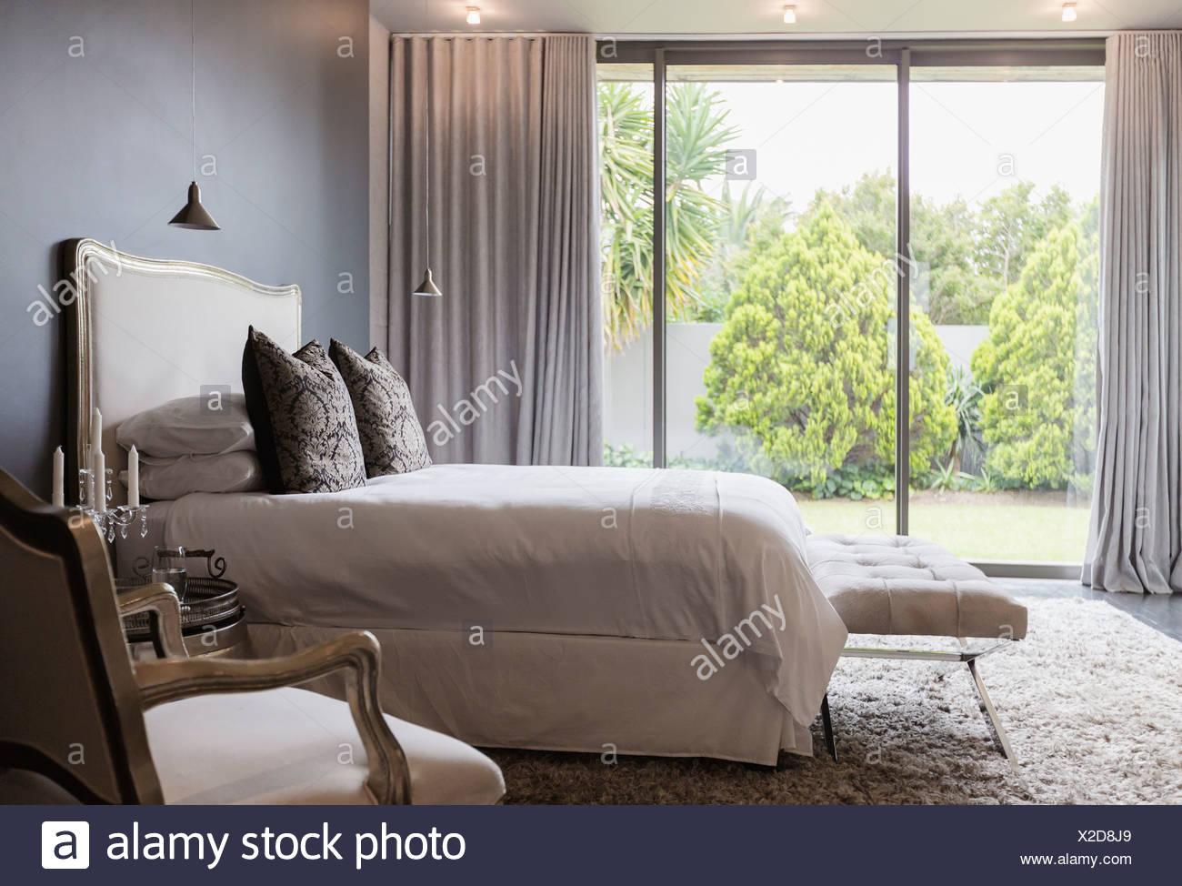 Luxury bedroom overlooking backyard - Stock Image