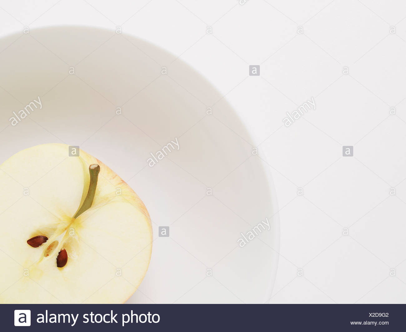 Half apple with core in white bowl - Stock Image
