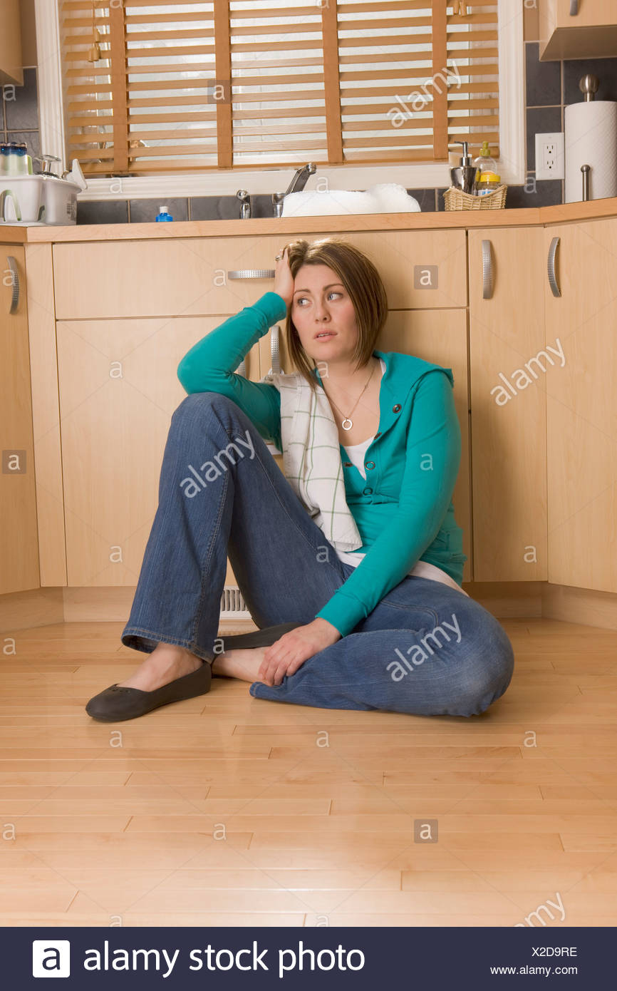 Woman sitting on the floor of the kitchen - Stock Image
