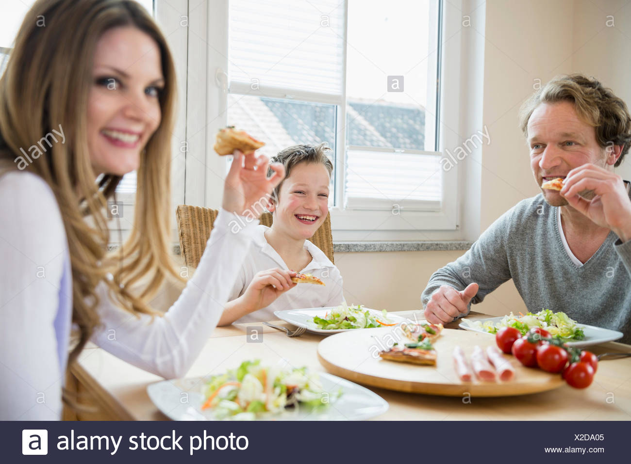 Family eating pizza and salad at home - Stock Image