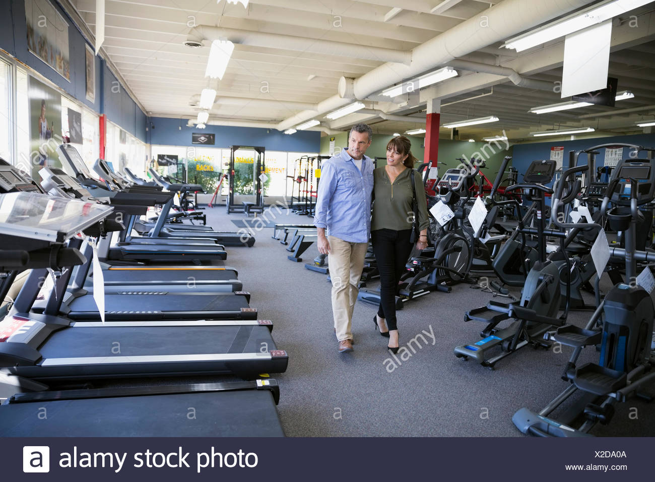 Couple browsing cardio machines in home gym equipment store stock