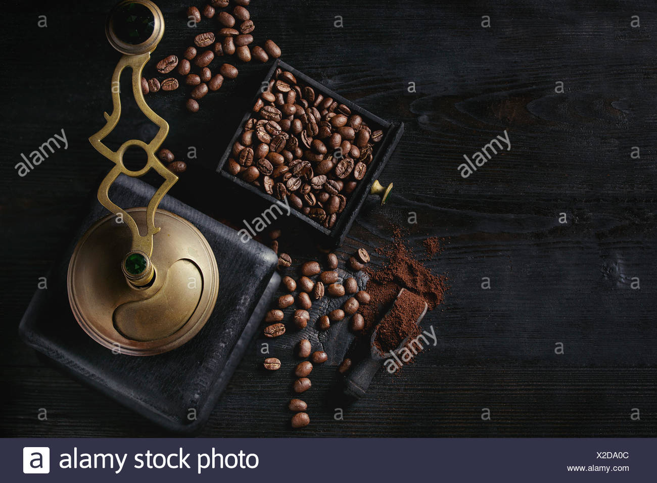 Roasted coffee beans and grind coffee in wood box with vintage coffee grinder and scoop over black wooden burnt background. Top view with space. Stock Photo