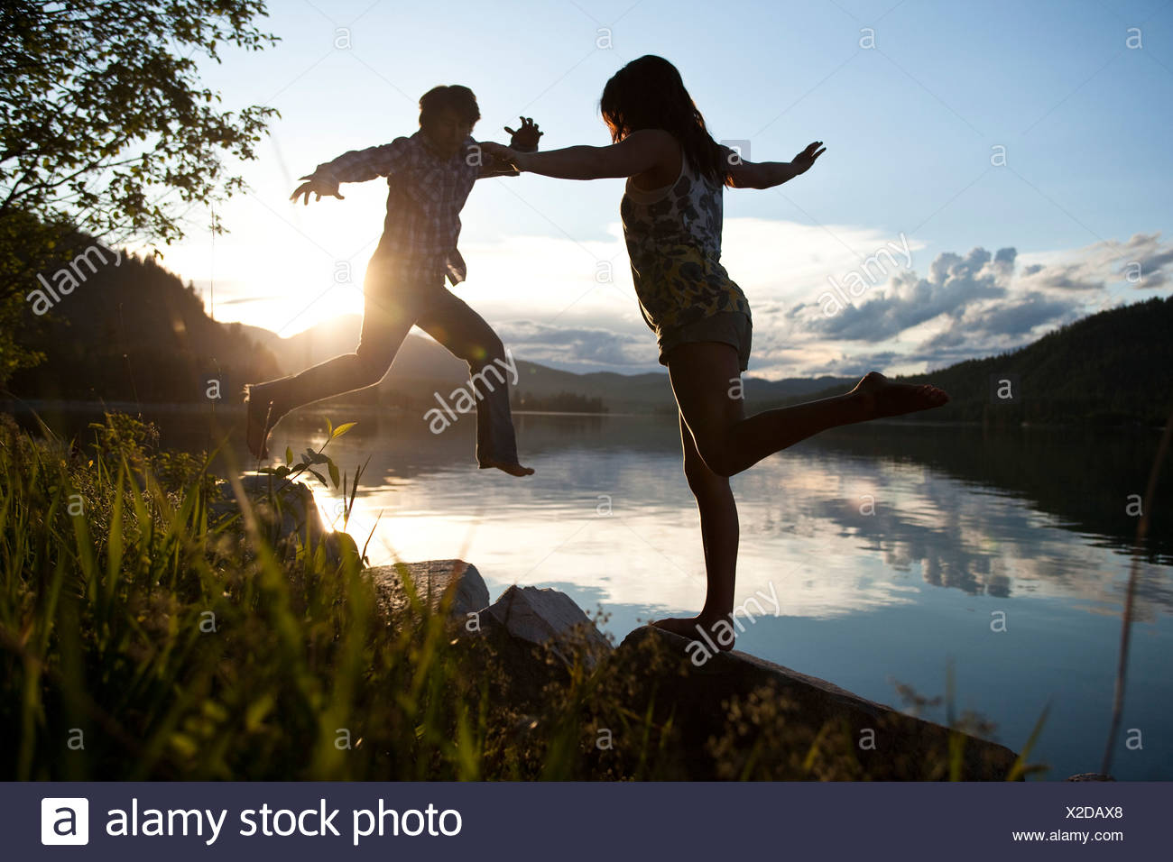 Two young adults balancing on rocks at sunset next to the lake. - Stock Image