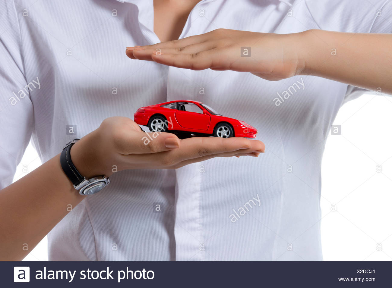 Midsection of insurance agent covering toy car against white background - Stock Image