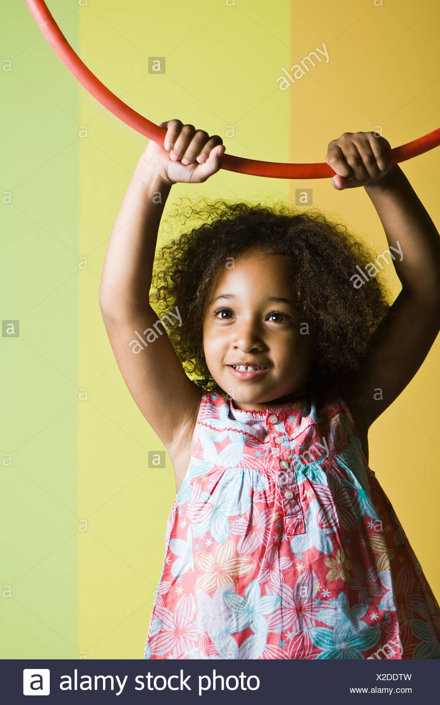 Little girl holding plastic hoop above her head - Stock Image