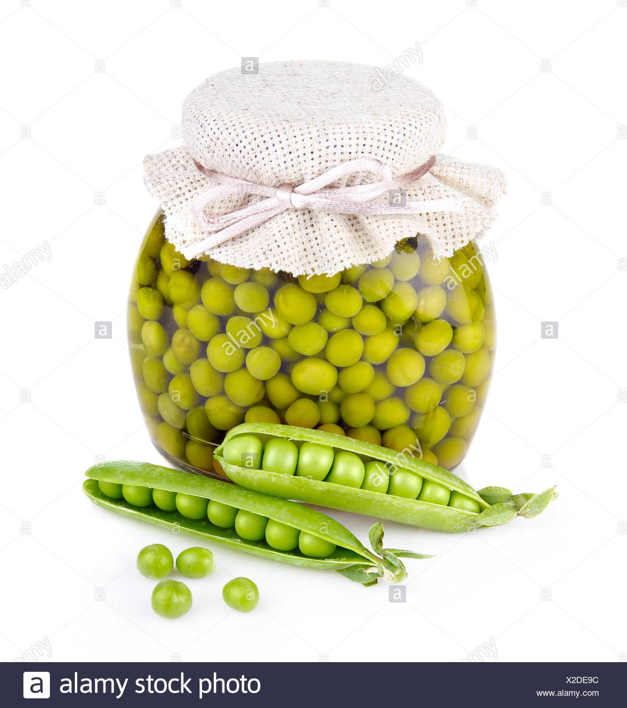 Glass jar of preserved peas and pods isolated on white - Stock Image