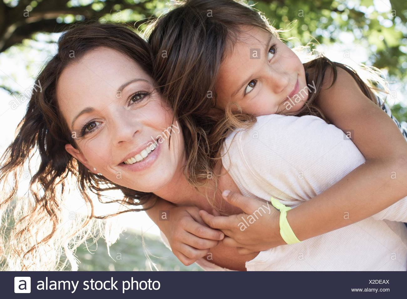 Portrait of mature woman giving daughter piggy back in park - Stock Image