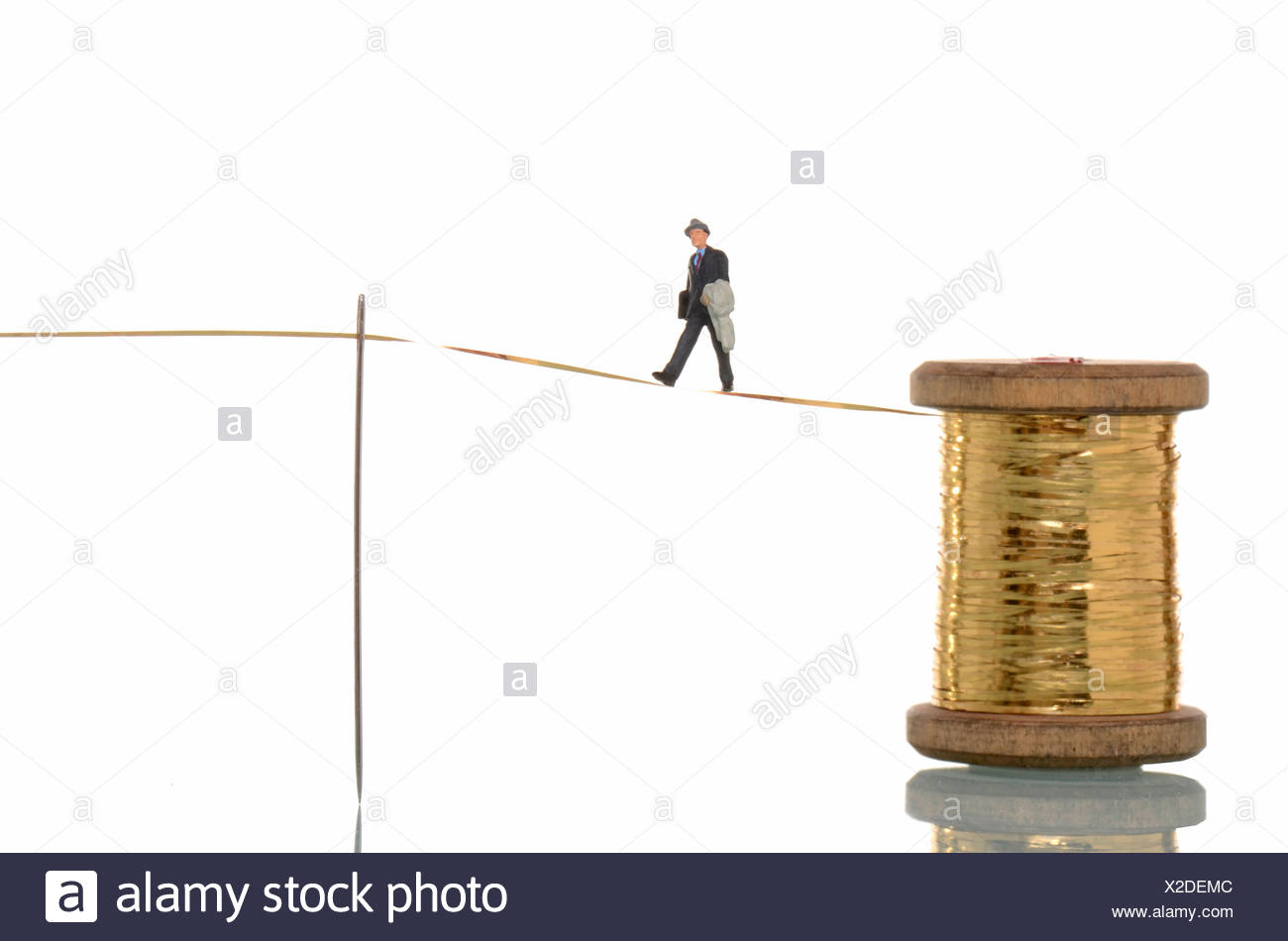 Business man figure balancing on golden thread, symbolic image for the highwire act of gold prices - Stock Image