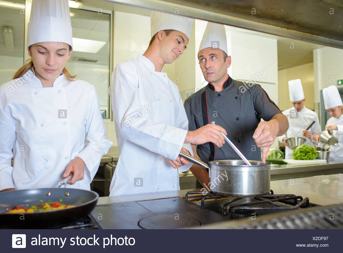 Chef advising cookery student - Stock Image