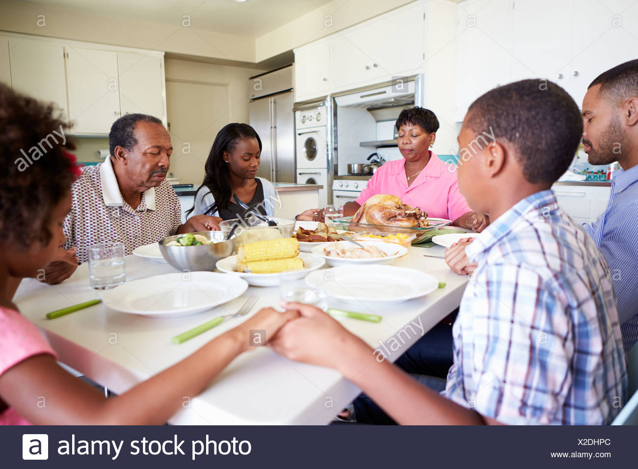 Multi-Generation Family Saying Prayer Before Eating Meal Stock Photo