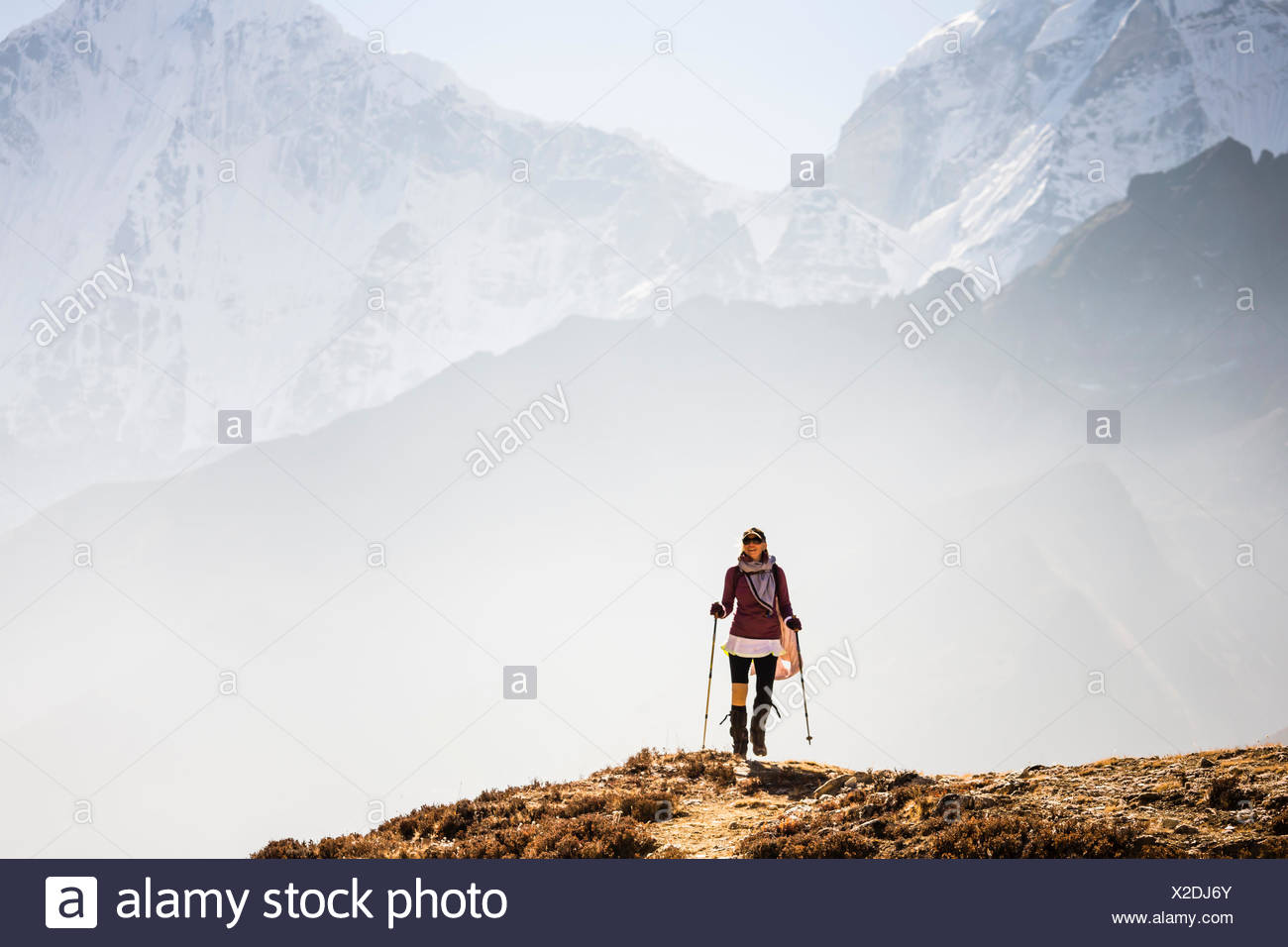 A woman is hiking a trail, Sagarmatha National Park, Khumbu region, Nepal. - Stock Image
