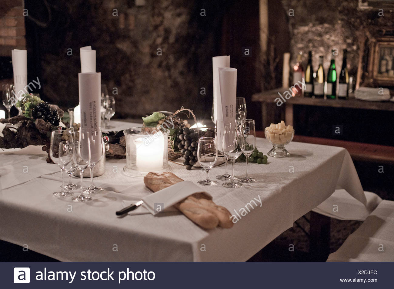 Classy set table in a wine cellar with baguette - Stock Image