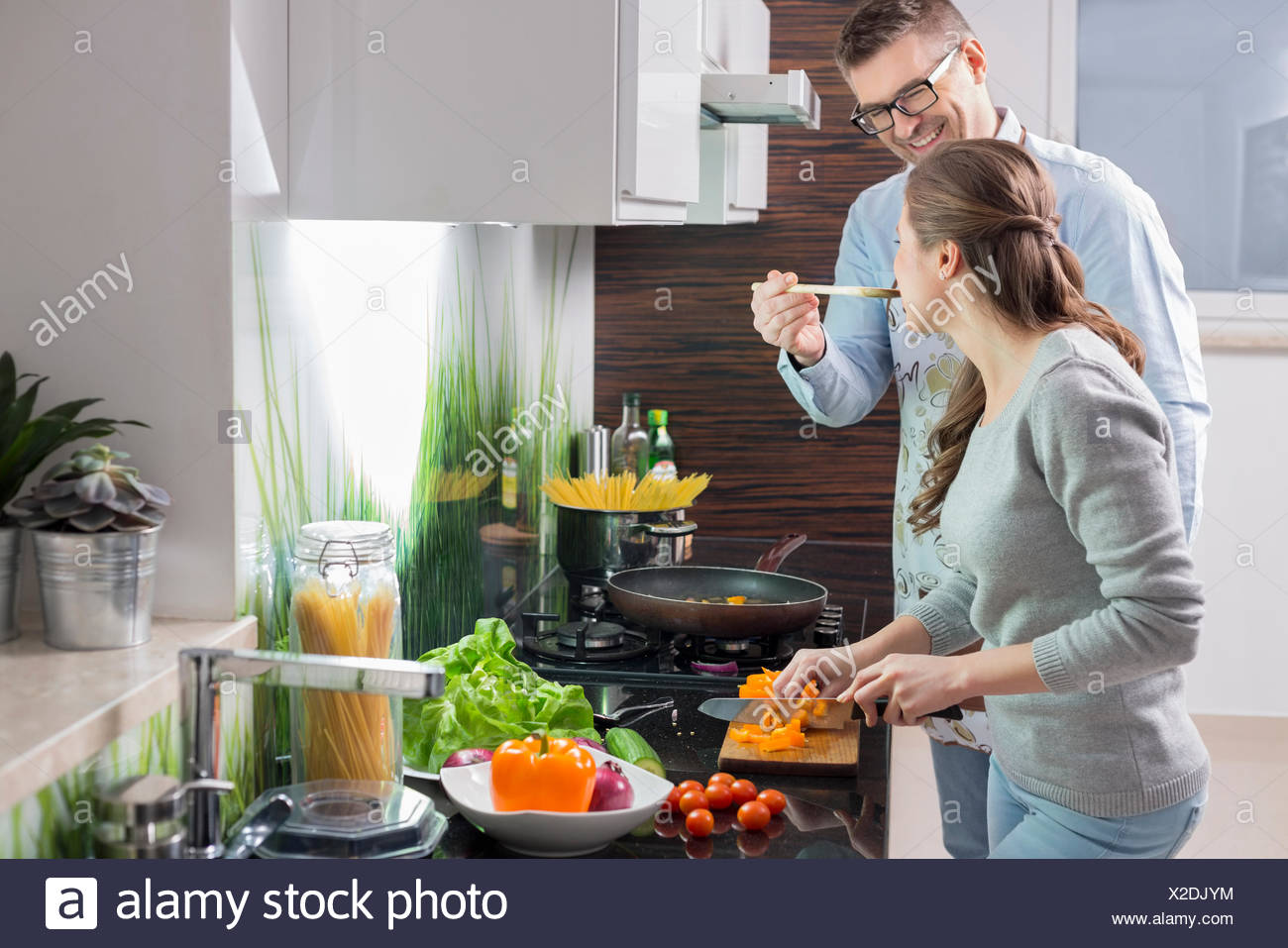 Happy man feeding food to woman cutting vegetables in kitchen - Stock Image