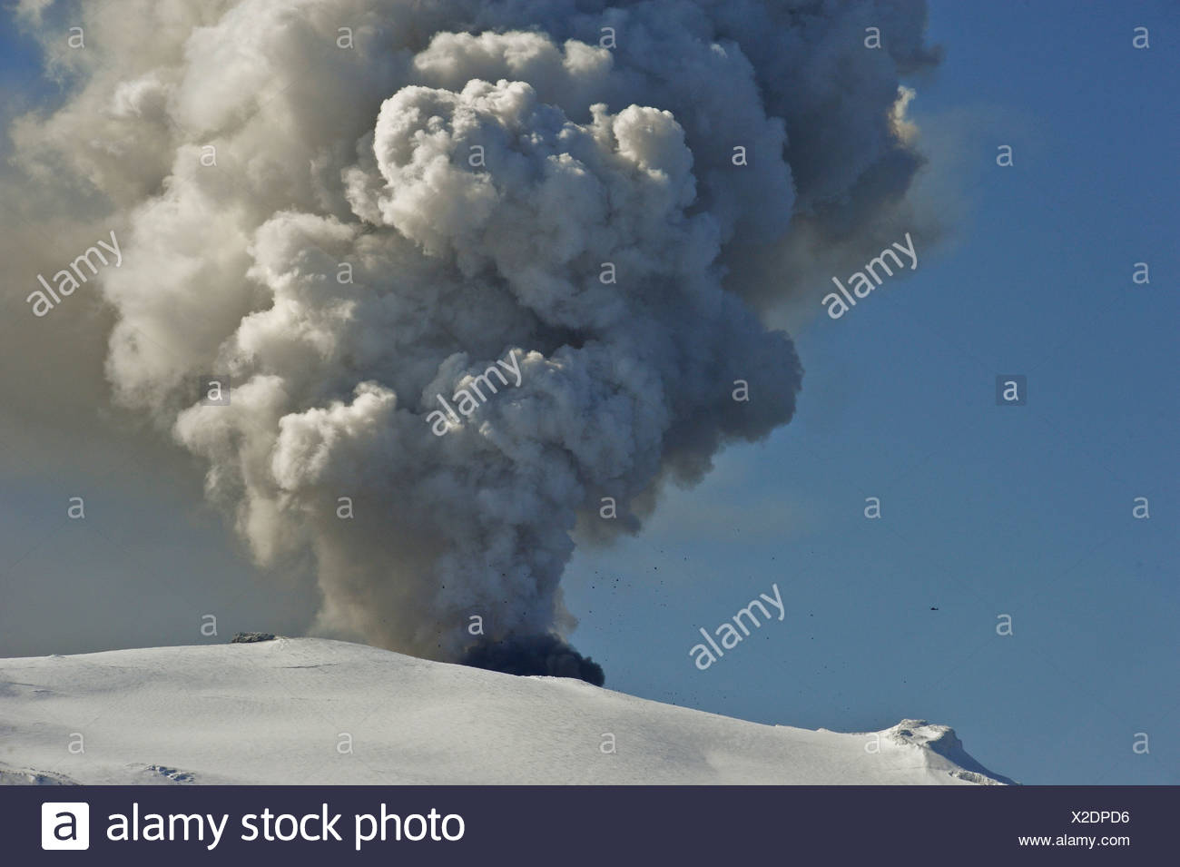 A helicopter flying in close proximity to the crater of Eyjafjallajoekull Volcano, while large lava bombs are being hurled into - Stock Image