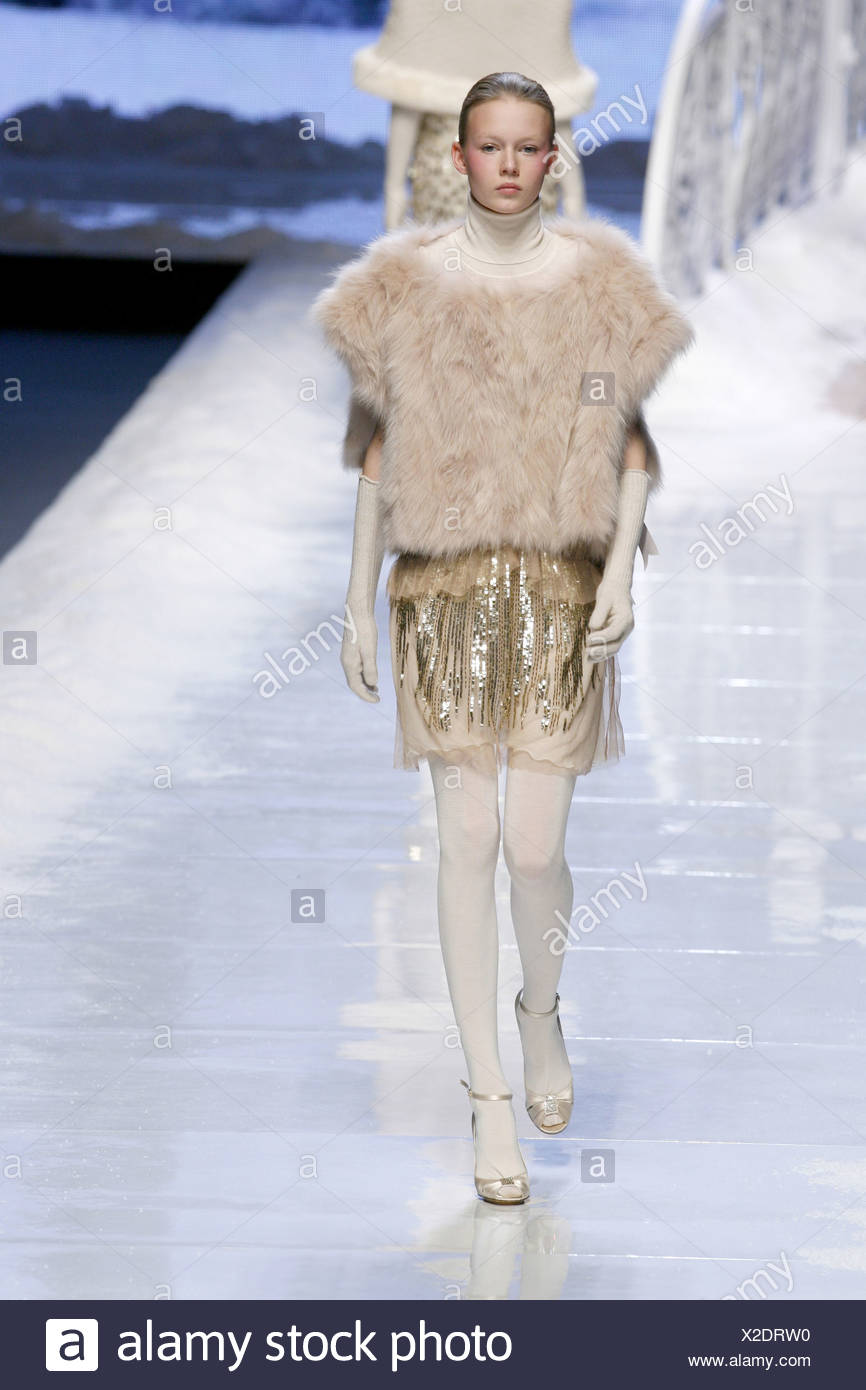Blu Girl Milan Ready to Wear Autumn Winter Model wearing a fur poncho, cream polo necked top, and short skirt gold sequin - Stock Image