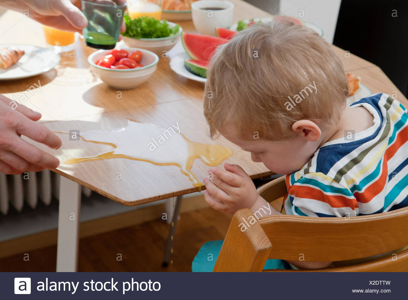 Male toddler accidentallyspilling orange juice at breakfast table - Stock Image