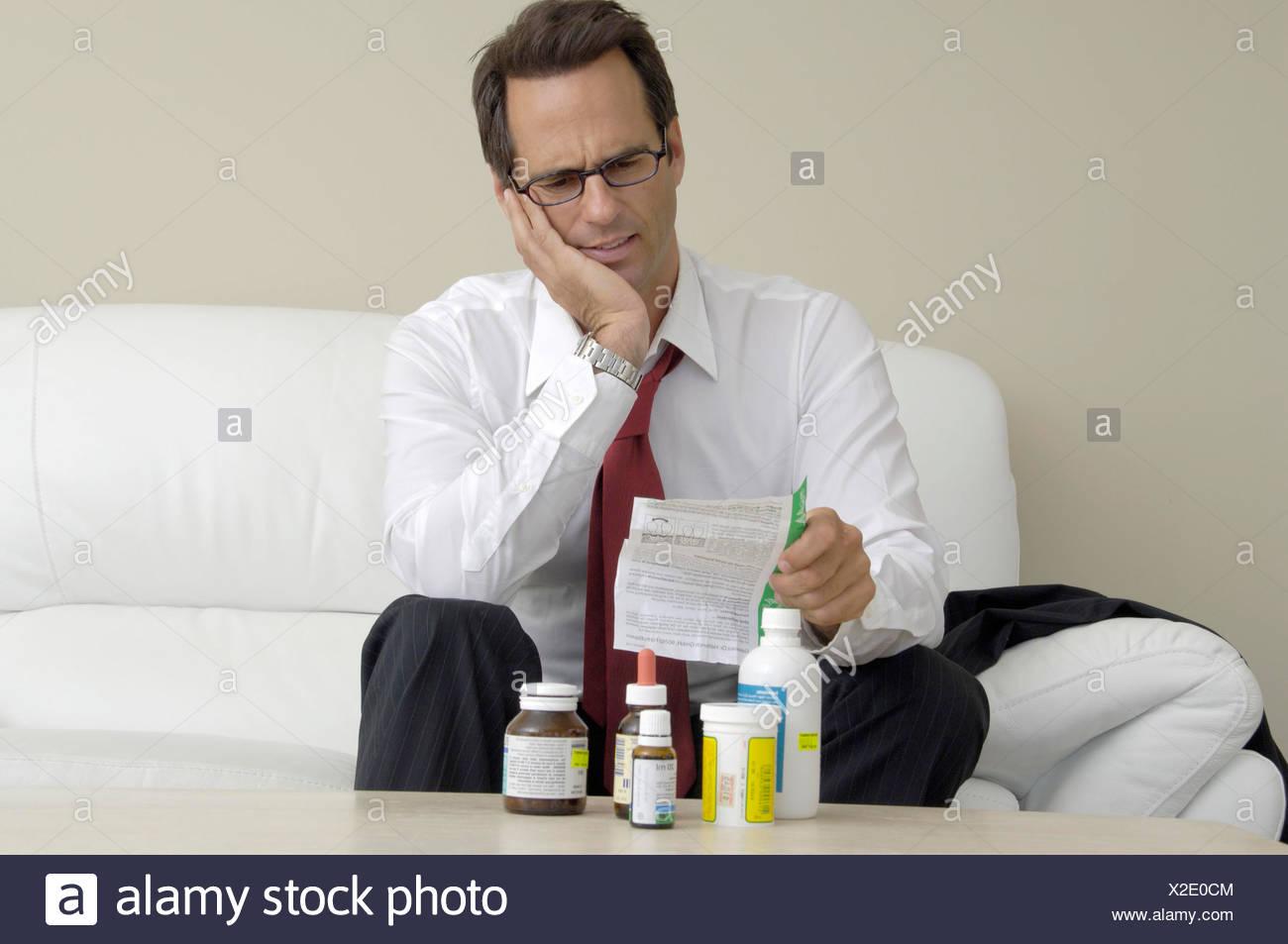 Man inside sitting sofa reading packing addition slip of paper medicines medicine medicament - Stock Image