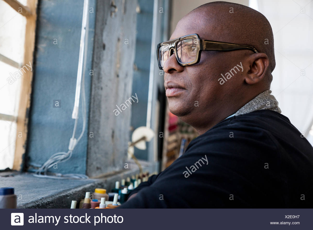 Portrait of man wearing glasses looking away - Stock Image