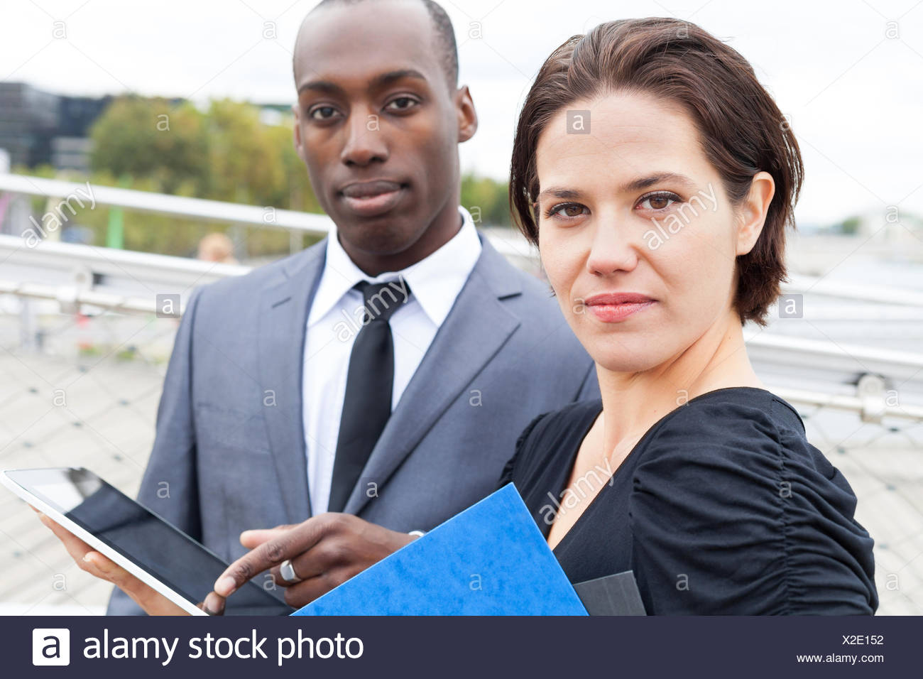 Portrait of business people with the man presenting something on electronic tablet Stock Photo