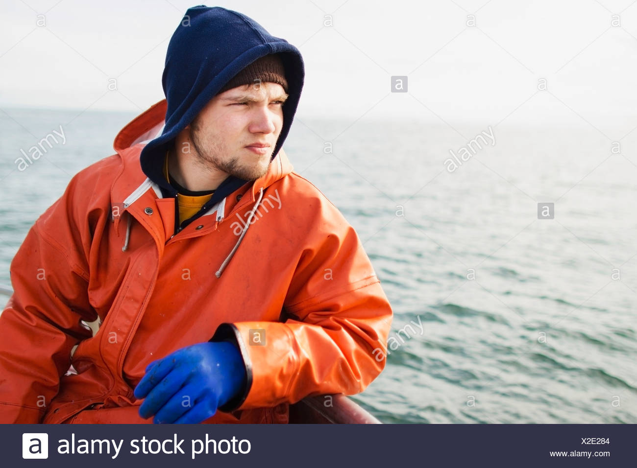 Rain Gear Clad Deckhand Takes A Break Sitting On The Rail Looking Out At The Net While Salmon Fishing On The Copper River Flats - Stock Image