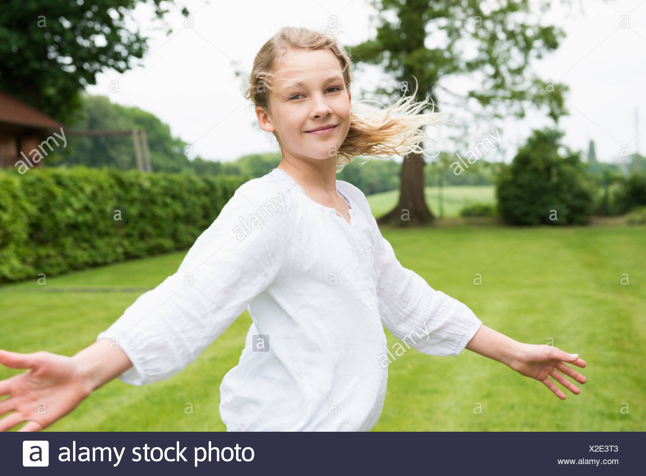 Girl wearing white top with arms out - Stock Image