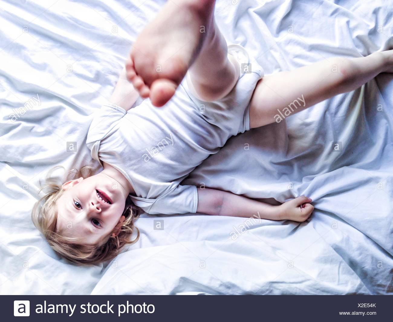 Boy lying on bed kicking his leg in the air - Stock Image