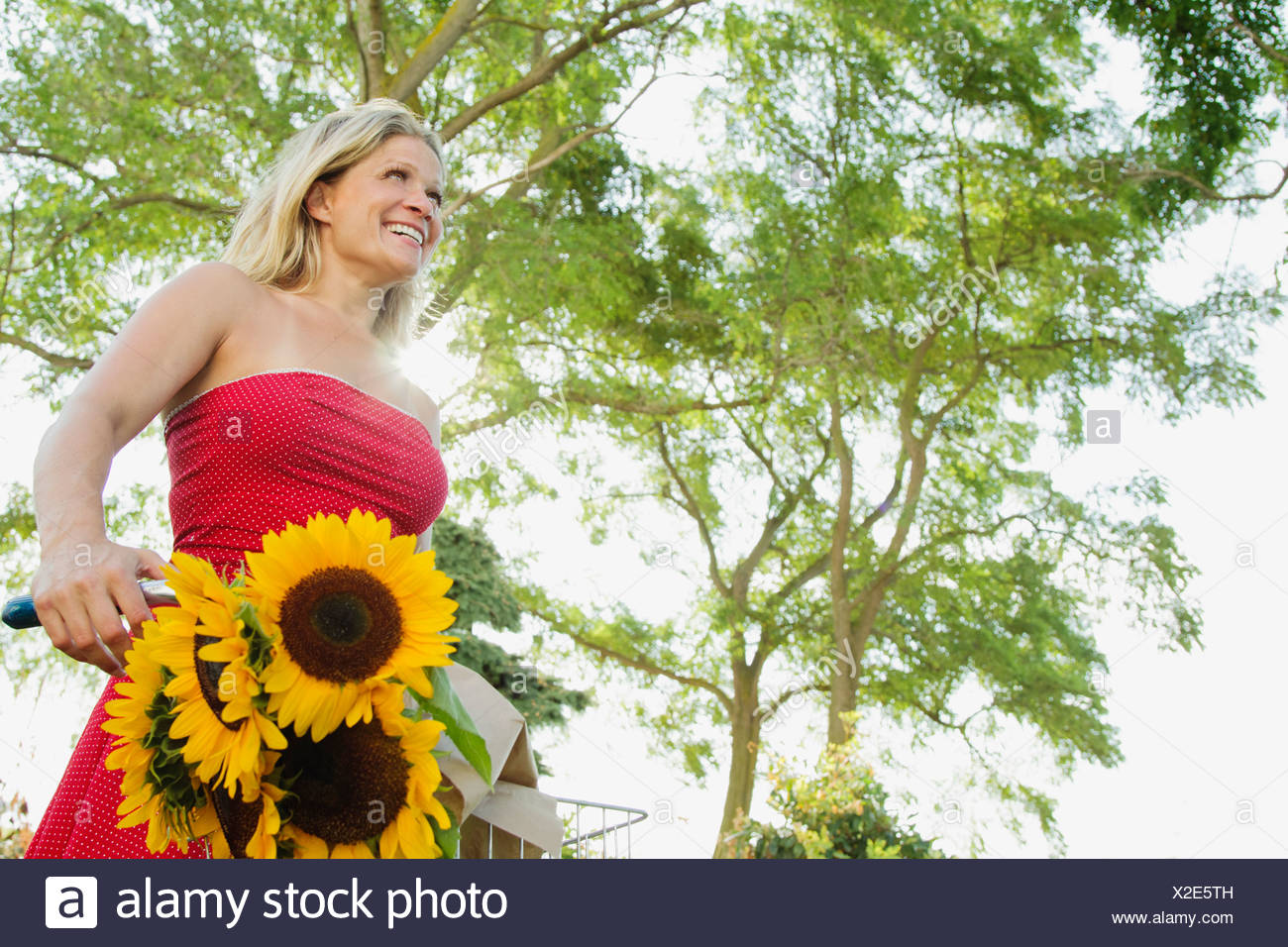 Woman standing with bicycle outdoors - Stock Image