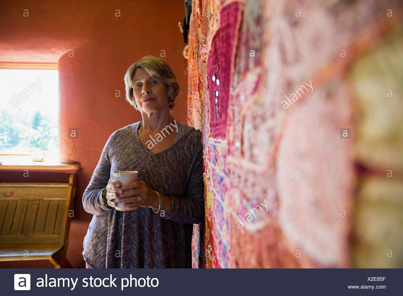 Portrait confident senior woman drinking coffee at tapestry Stock Photo