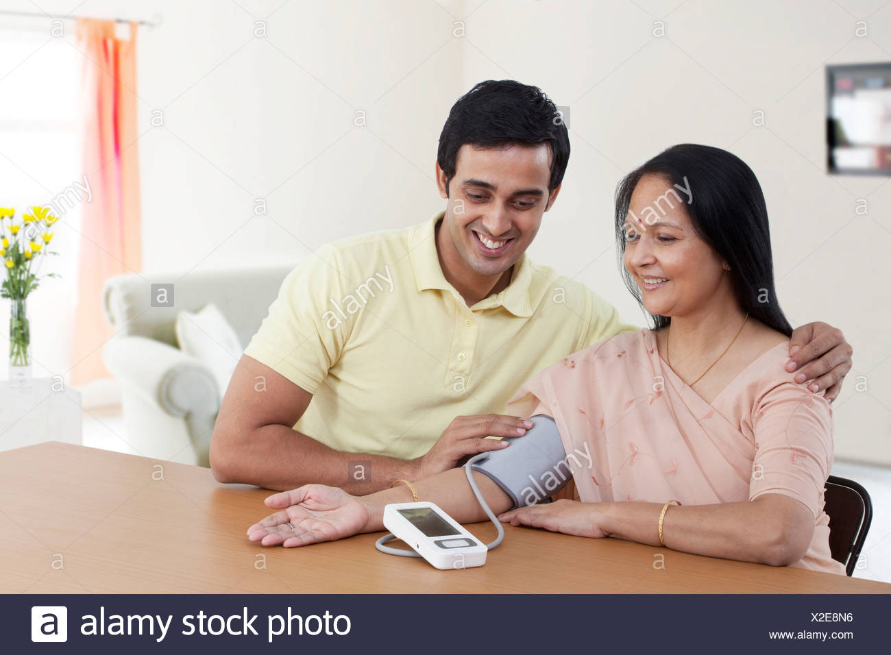 Mother and son looking at blood pressure gauge - Stock Image