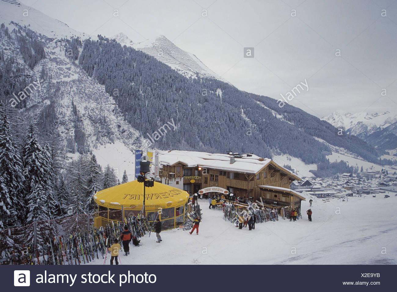 Austria, mountain Arl, St. Anton, ski hut, snow bar Mooserwirt, ski hut, Aprés ski, Apres ski, winter scenery, snow, mountain landscape, skis, put down, dusk, lighting, local view, skier, stop, call in Stock Photo