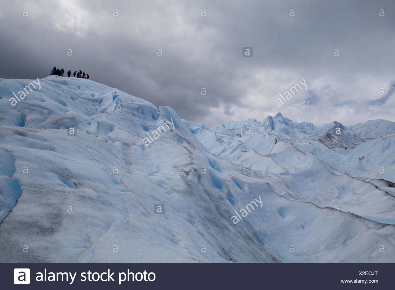 On top of the Perito Moreno Glacier: a group of persons show the dimensions of the landscape. - Stock Image