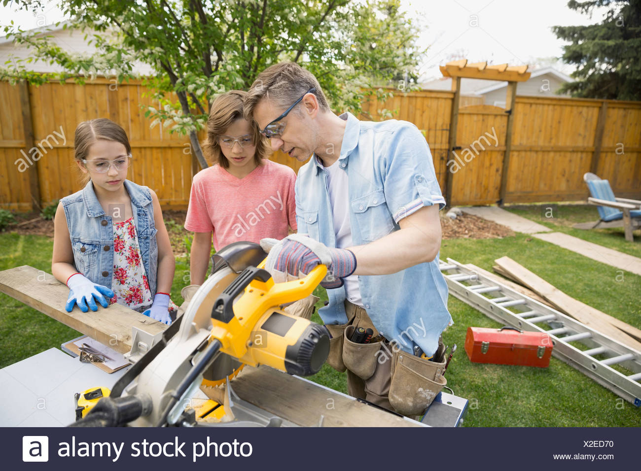 Father teaching children to use table saw - Stock Image