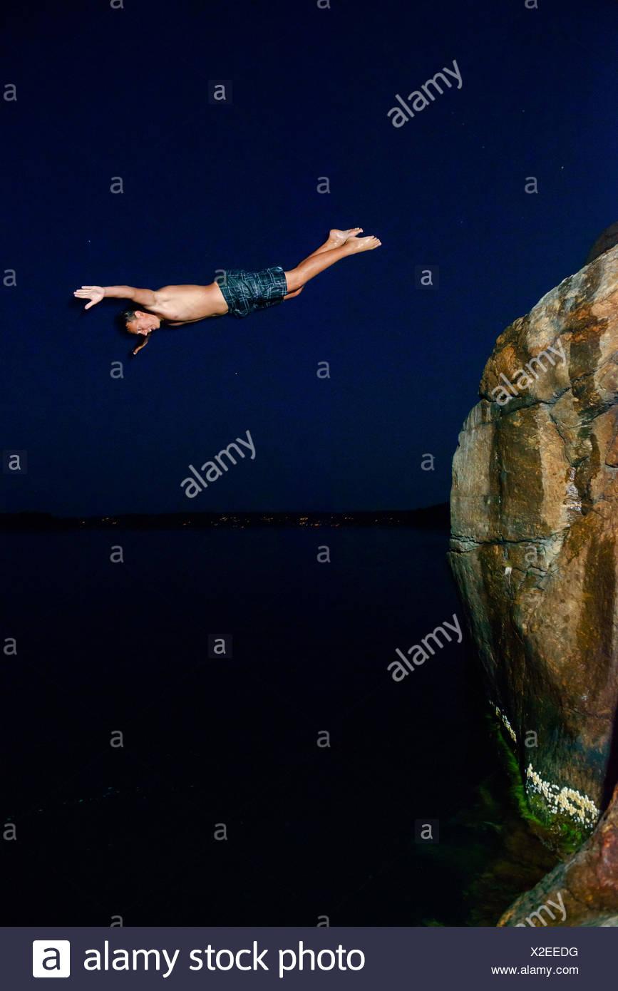 Man jumping into sea at night Stock Photo