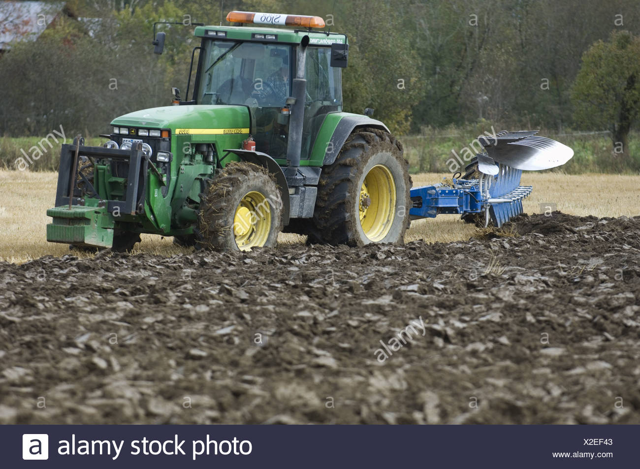 John Deere 8400 tractor pulling eight furrow reversible plough, ploughing stubble field, Sweden, autumn - Stock Image