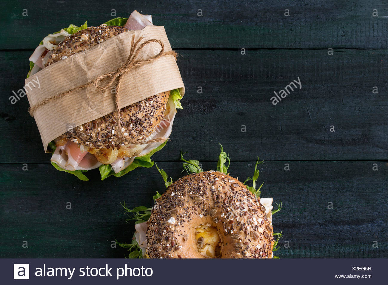 Two sprinkle seeds Whole Grain bagels with fried onion, scrambled eggs, green salad and prosciutto ham over dark wooden textured - Stock Image