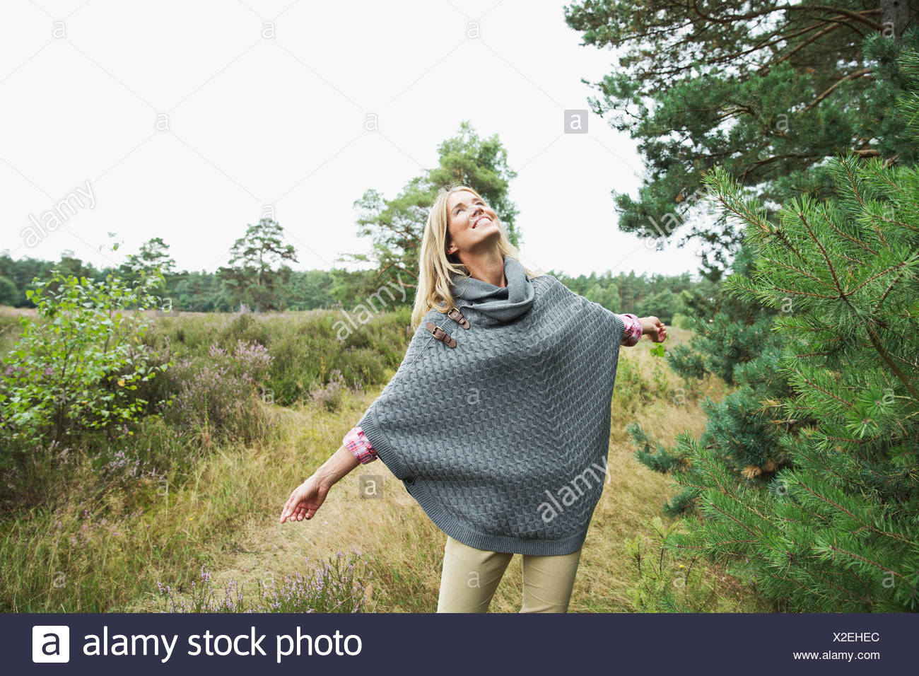 Mid adult woman wearing grey poncho looking up - Stock Image
