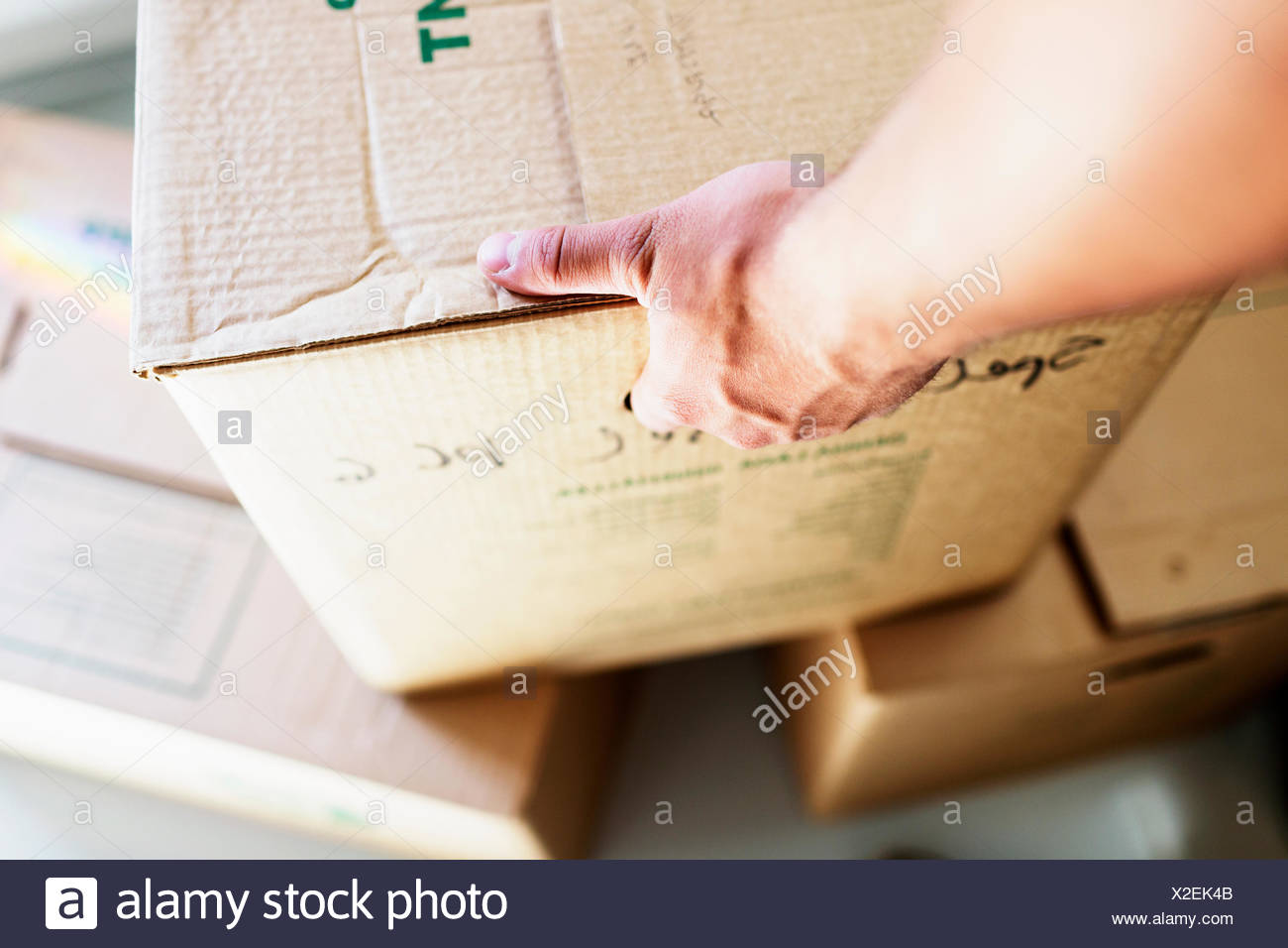 Cropped image of man's hand picking up cardboard box at new home - Stock Image