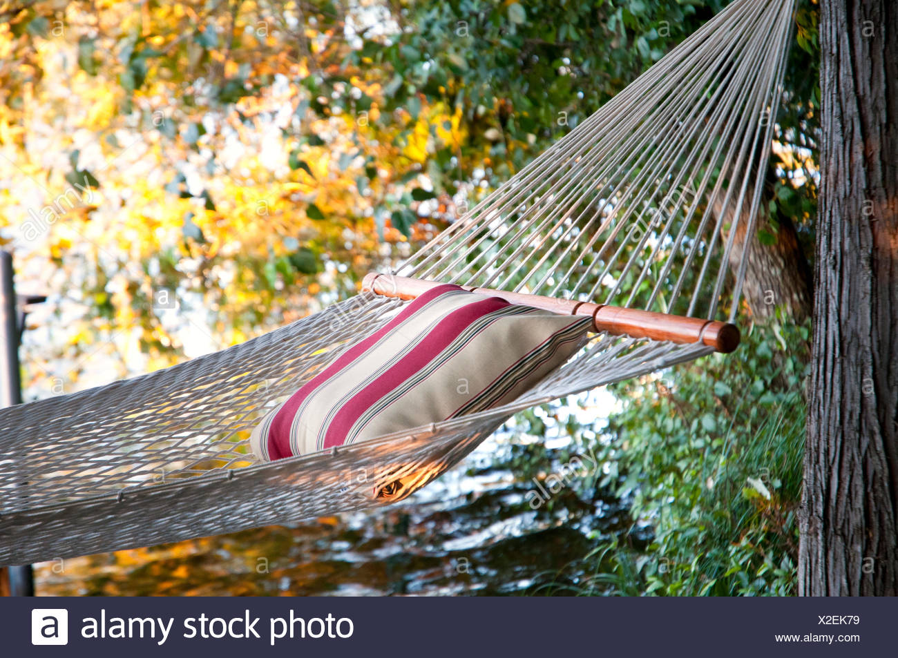 A hammock waits for a lazy afternoon by Langford Lake, near Victoria, BC Canada, a freshwater lake for swimming, relaxing and - Stock Image