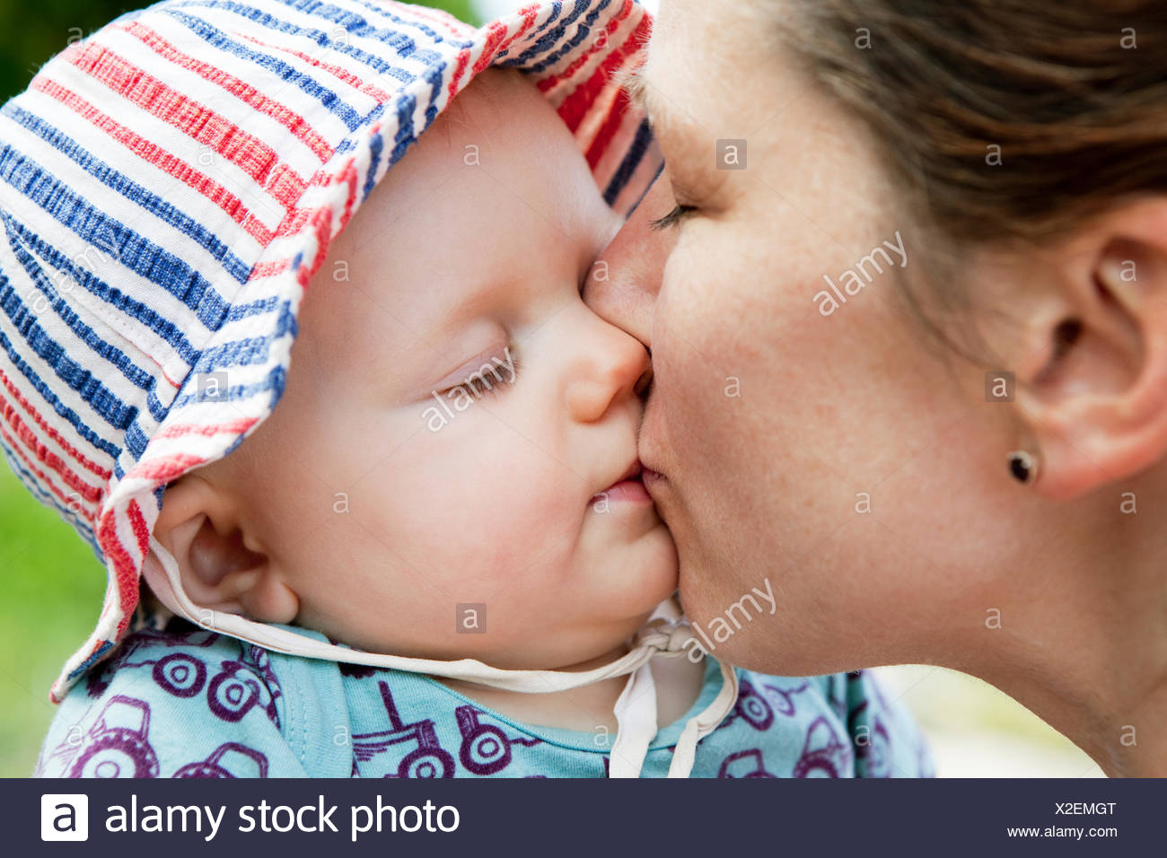 Woman kissing her baby daughter (6-11 months) - Stock Image