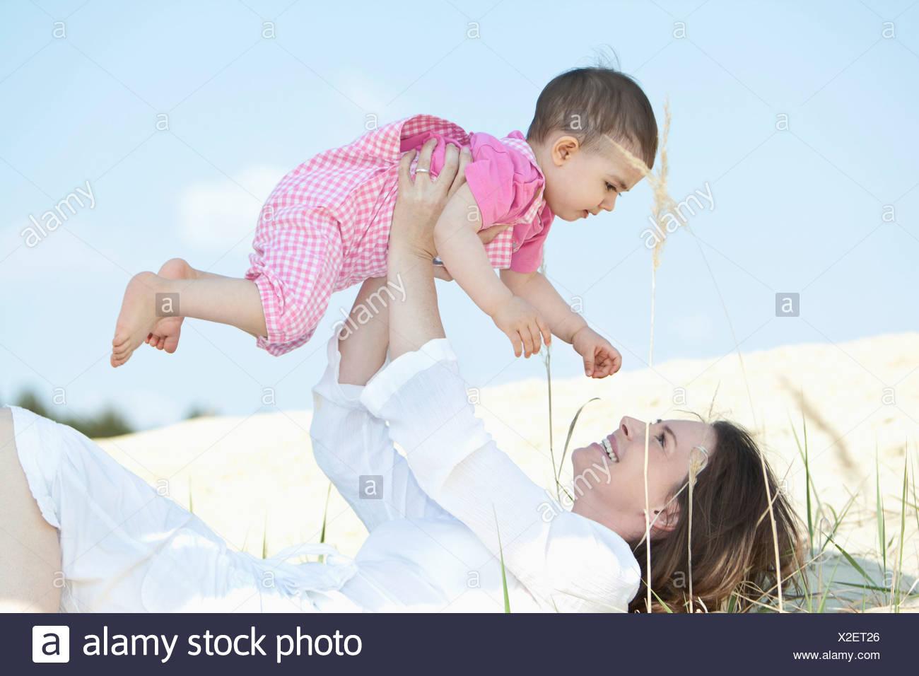 Germany, Bavaria, Mother lying and holding aloft baby girl - Stock Image